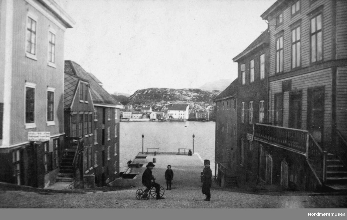 dublett - Vestre almenning på Kirkelandet i Krisitansund, som kom ut hvor vi omtrent finner Rica Hotell i dag: Langveien.  Her ser vi fra enden av Storgata og ned mot Lyhsallmenningen, med boliger og forretninger nærmest på begge sider. Mot sjøen ligger bryggene. I bakgrunnen ser vi litt av Innlandet, og til venstre på I. ser vi Knudtzongården som ble revet i 1979. Ellers så ser vi midt på gata tre unger, hvor den ene er på en trehjulsykkel. Fra Nordmøre Museums fotosamlinger.
