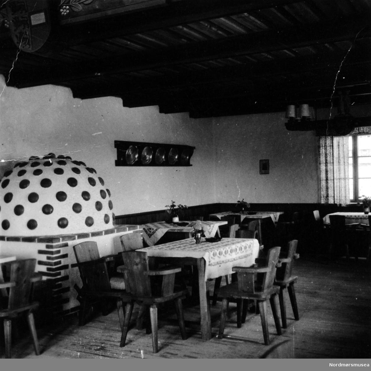 Foto fra en kantine, eller et større stuelokale med peis. Fotoet er fra firmaarkivet til en som var aktiv nazist under andre verdenskrig. Datering er fra perioden 1940 til 1945, og kan være fra 1942 basert på datering av et annet bilde i samme serie. Fra Nordmøre Museums fotosamlinger.