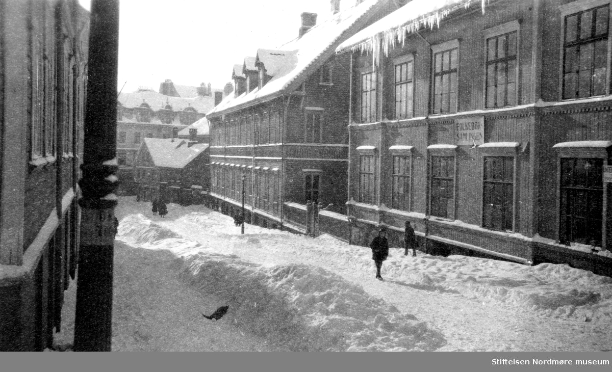 Skilt: Folkeboksamlingen. Biblioteket i Kristiansund, i Nedre Enggate. Enggatens Pikeskole er nabo til venstre. vinter, snø. ca 1880? Fra Nordmøre Museum sin fotosamling.