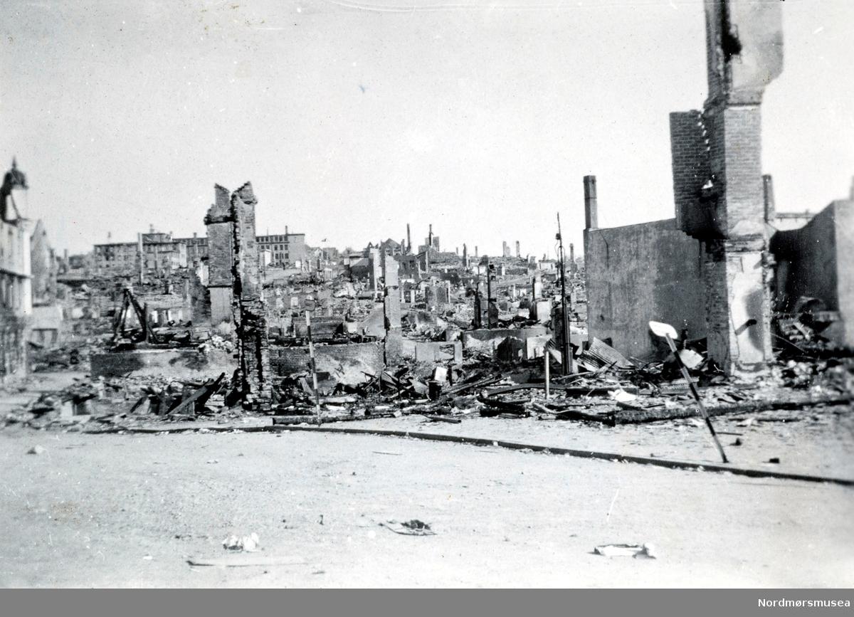 """Krigen har her kommet til Kristiansund. Etter nazistenes herjinger i perioden 28. april til 1. mai 1940 ligger nå store deler av byen i ruiner. Her ser vi fra ruinene på Kirkelandet.   Det totale antall brente bygg var 767, hvor 605 av disse var på Kirkelandet og 162 på andre """"land"""" i Kristiansund. Her fantes det til blant annet tilsammen 3906 boliger ifølge boligtellingen av 1938, og av disse brant 2162 boliger ned og 7099 mennesker ble husløse. I tillegg til de 767 brente byggene brant 36 fiskepakkehus ned til grunnen, hvorav 34 lå på andre """"land"""". Verdien av de brente byggene beløp seg til kroner 26,9 millioner for Kirkelandet (kroneverdi per 1940) eller tilsammen 30,6 millioner kroner (kroneverdi per 1940) for hele byen.   Fotoserie gitt av Bodil Øverland. Se reg. nr. KMb-1988-037.0001 til KMb-1988-037.0031. Fra Nordmøre Museums fotosamlinger.   Kilde: Gjenreisningsproblemer i Kristiansund. Fremlagt ved gjenreisningsinstituttet i Kristiansund. Juli 1945. Side 16. EFR2015"""
