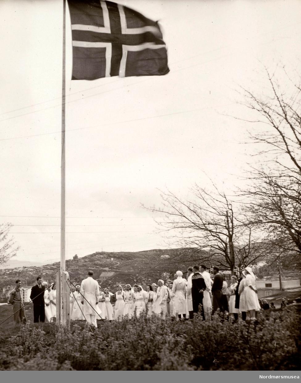 """""""Overlegen taler."""" Foto fra 8. mai 1945, hvor vi ser en gruppe sykesøstre har heist det norske flagget på frigjøringsdagen, og overlegen holder en tale Bildet er trolig fra Kristiansund, men kan være fra Oslo, hvor vi ser fra sykepleierstudentene ved Røde Kors' søsterhjem. Fra Ida M. Knudtzons fotosamlinger, nå en del av Nordmøre Museums fotosamlinger."""