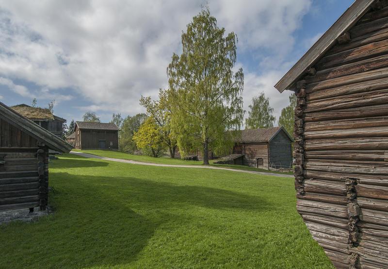 Tun med grå tømmerbygninger. (Foto/Photo)