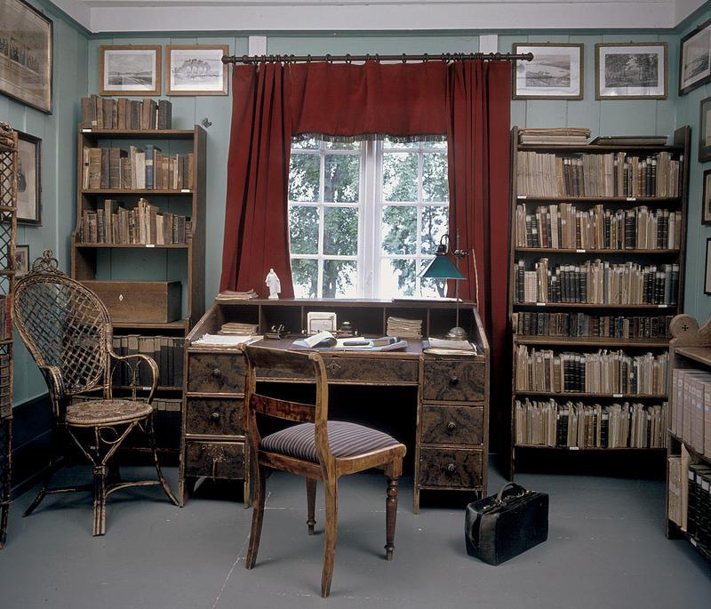 Interiør; bibliotek med bokhyller på begge sider av et vindu med røde gardiner, skrivebord og stol foran vinduet. (Foto/Photo)