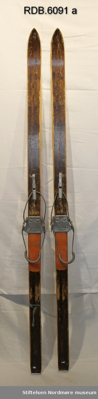 Et par brune, laminerte ski med trekvite kanter. Merker etter logo på skituppene. Stålkanter bak. Flate skitupper. Skiene er oppskrapte og slitt og det er malingsrester bak på venstre ski. Påmontert Gresvig Kandaharbindinger og orange, faststiftede fotplater i hardplast.