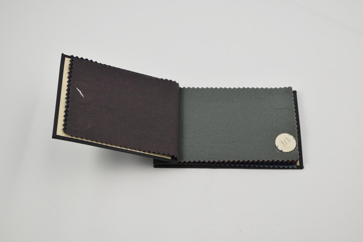 Prøvebok med 11 prøver. Tynne monokrone ullstoff. Alle stoffer er merket med en rund papirlapp festet med melallstifter hvor nummer er påskrevet for hånd.   Stoff nr. 801 (grå), 802 (grå), 803 (grå), 804 (brun), 805 (fiolett), 806 (blå),  807 (blå), 808 (grønn), 809 (sort), 810 (grå), 811 (sort).