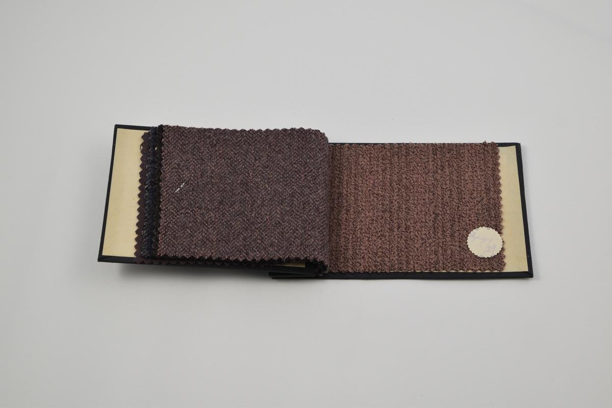 """Prøvebok med 6 prøver. Middels tykke ullstoff med diskret mønster, særlig i form av striper. Denne prøveboken inneholder flere ulike designnummere av kvaliteten """"Ryvingen"""". Alle stoffer er merket med en rund papirlapp festet med metallstifter hvor nummer er påskrevet for hånd.  Stoff nr. Ryvingen/35 (fiolett), Ryvingen/55 (blå), Ryvingen/68 (blå), Ryvingen/74 (grå), Ryvingen/79 (fiolett), Ryvingen/29 (rosa)."""