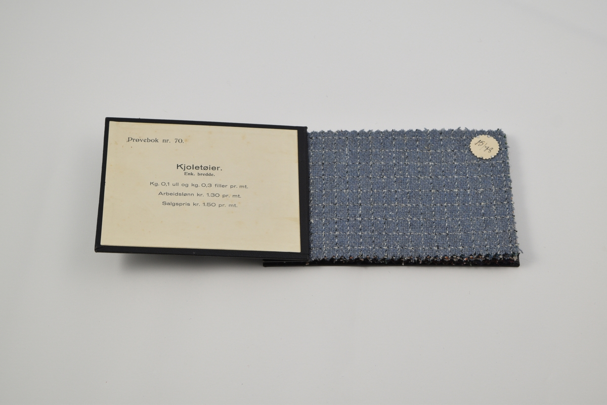 Prøvebok med 7 prøver. Middels tykke ullstoff med ruter og striper. Prøveboken innholder stoffer med ulike designnummere, innen kvalitetsnummeret 15. Alle stoffer er merket med en rund papirlapp festet med metallstifter hvor nummer er påskrevet for hånd.  Stoff nr. 15/78 (blå), 15/81 (grønnblå), 15/82 (grå), 15/87 (brun), 15/88 (rød), 15/93 (brun), 15/96 (sort/mørk blå).