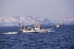 To fiskebåter på havet, Lofoten, med Lofotveggen i bakgrunne