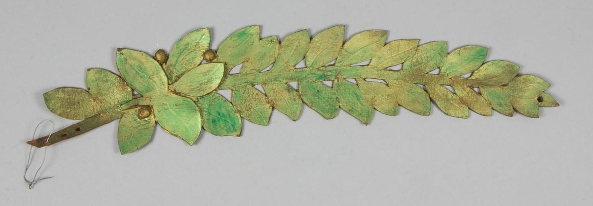 Lagerkrans, del av, tillverkad av läder. Målad i guld och grönt. Genombruten.