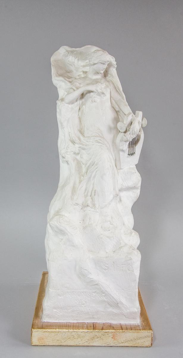 Kvinna, Sappho, stående, håller en trälyra med metallsträngar i ena handen. I andra handen, tryckt mot bröstet, blommor. Lutad mot klippformation.