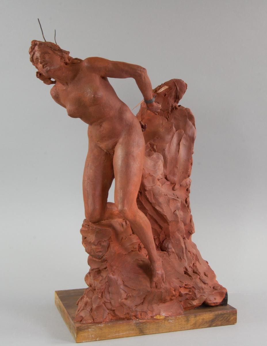 Andromeda, naken i helfigur med bakbundna händer, stödjer sig mot en klippa.