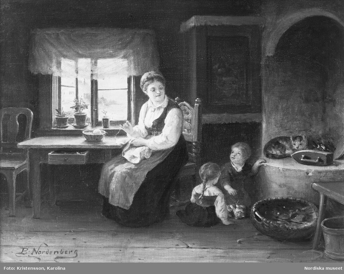 Målning av Bengt Nordenberg föreställande interiör med bondhustru från Blekinge som sitter och syr vid fönstret i allmogemiljö. Två barn leker på golvet framför den öppna spisen där en randig katt ligger och värmer sig.