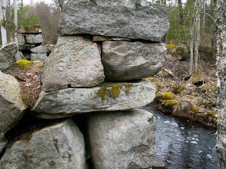 Sågverkslämning Foto av minnesinskription. På sågverksruinens nordvästra hörn är bokstäverna SPSM inhuggna i en sten (upp och ner). Lämningarna benämns Häradsbäcks sågkvarn av ortsbor. På platsen finns en kvarn markerad på Häradskartan från år 1660 (Ruuths).Raä 505 b, 2006-04-20, reg i FMIS.
