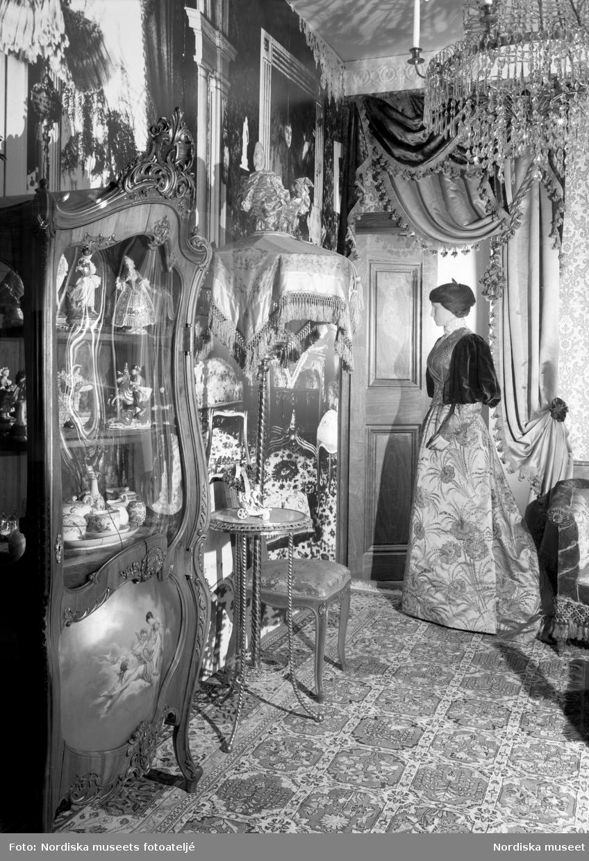 """Interiör från en borgerlig bostad i block 3 på Nordiska museets jubileumsutställning """"Svenskens 100 år - känn dig själv"""". I ett rum inrett enligt det sena 1800-talets överlastade ideal med mycket möbler och textilier står en docka föreställande en kvinna i tidstypisk dräkt."""