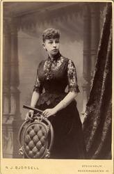 Porträtt (knäbild, halvprofil) av en kvinna i mörk festklänn