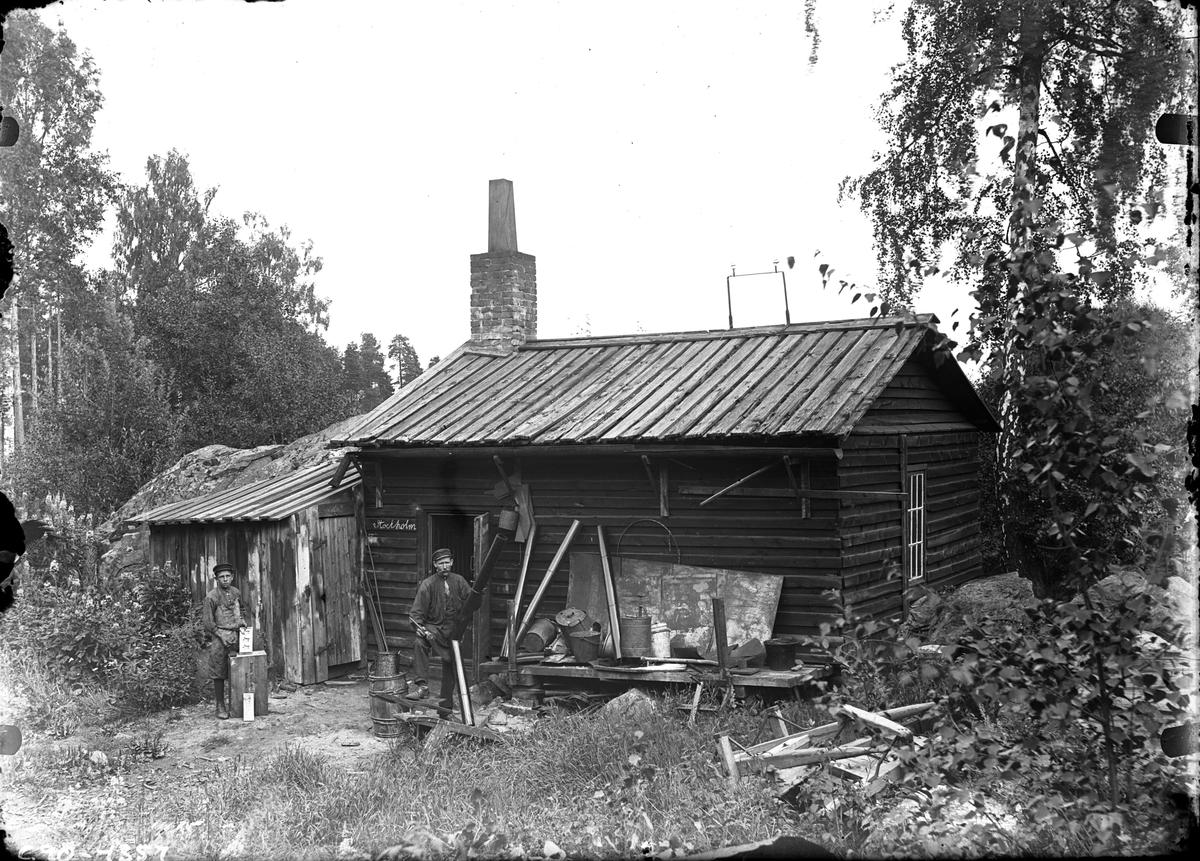 """En man och pojke utanför skogskojan """"Stockholm""""."""