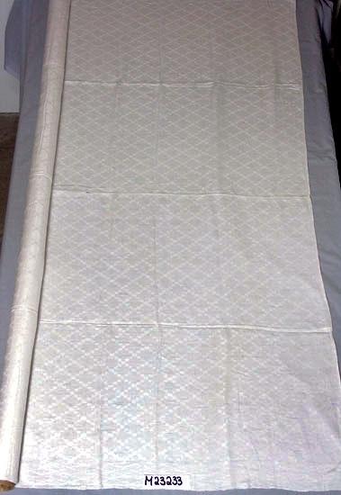 Duk i linne, handvävd dräll.  Rutigt mönster (romber).  Vävd i två våder som sytts ihop för hand.  Inskrivet i huvudkatalogen 1978. Funktion: Bordduk
