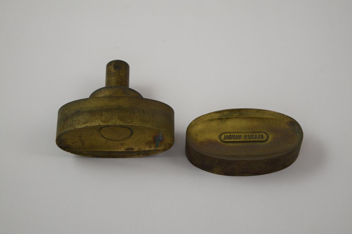Oval såpeform i to deler for produksjon av såper ved Saanums Sepefabrikk AS i Mandal. Sannsynligvis jern med messing utenpå.  Konkav topp (A) og bunn (B) med relieff/motiv/tekst for trykk. Ulik motiv/tekst i topp og bunn. Toppen med sirkulært motiv, bunnen med tekst.