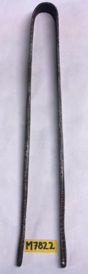 Nypsax av järn bestående av ett tunt plattjärn  som böjts på mitten och utgår i två ben, vilka  avsmalnar mot ändarna. Verktyget användes för att dra ut en tunn glas- tråd, som lades runt fönsterglascylinderns kappa för att skränga bort denna. Invent. 1996-03-11 och 2006-06-28. Inskriven i huvudkatalogen 1935. Funktion: Att skränga kappan på fönserglas