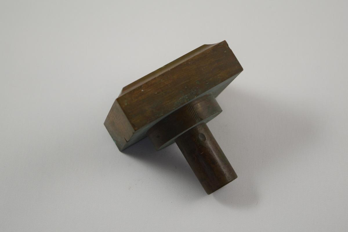 Rektangulær såpeform for produksjon av såper ved Saanms Sepefabrikk i Mandal. Kun topp, mangler antageligvis bunn, eller kan ha vært brukt som et stempel. Stempelflate med nedsenket rektangel med nedsenket tekst. Rette hjørner.