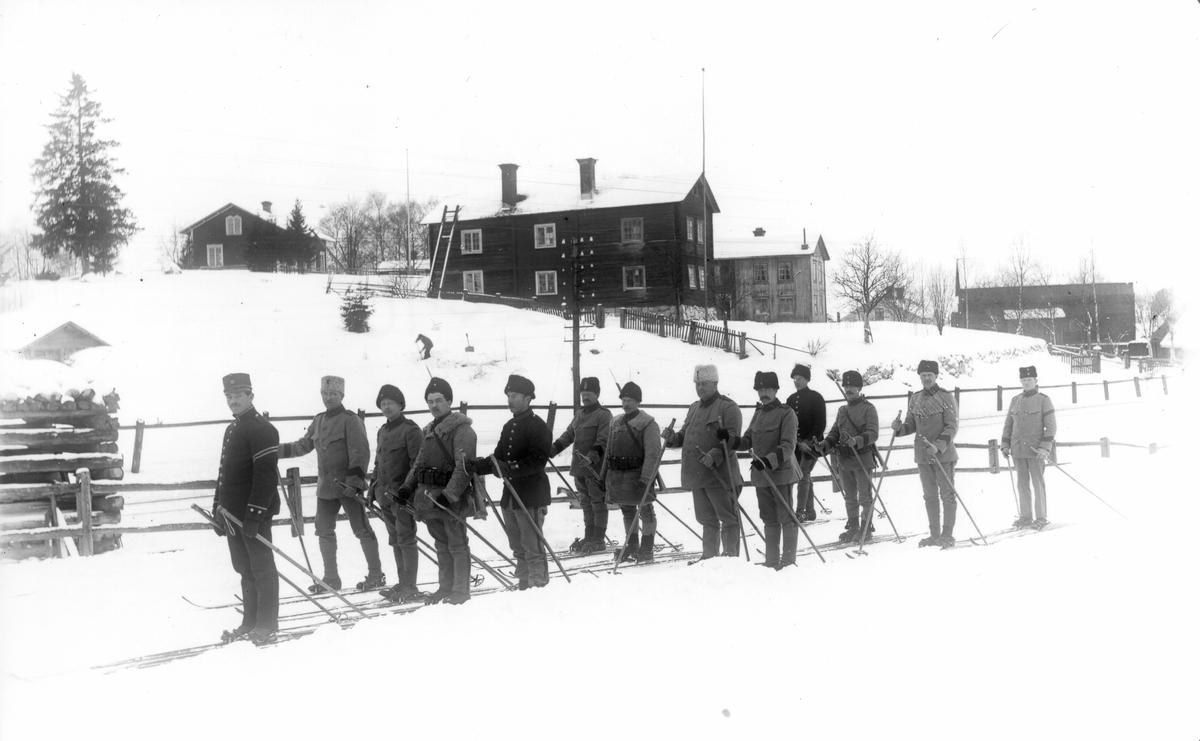 Militärer på skidor på åkern nedanför Ol-Ers. Gamla skolan syns längst upp.