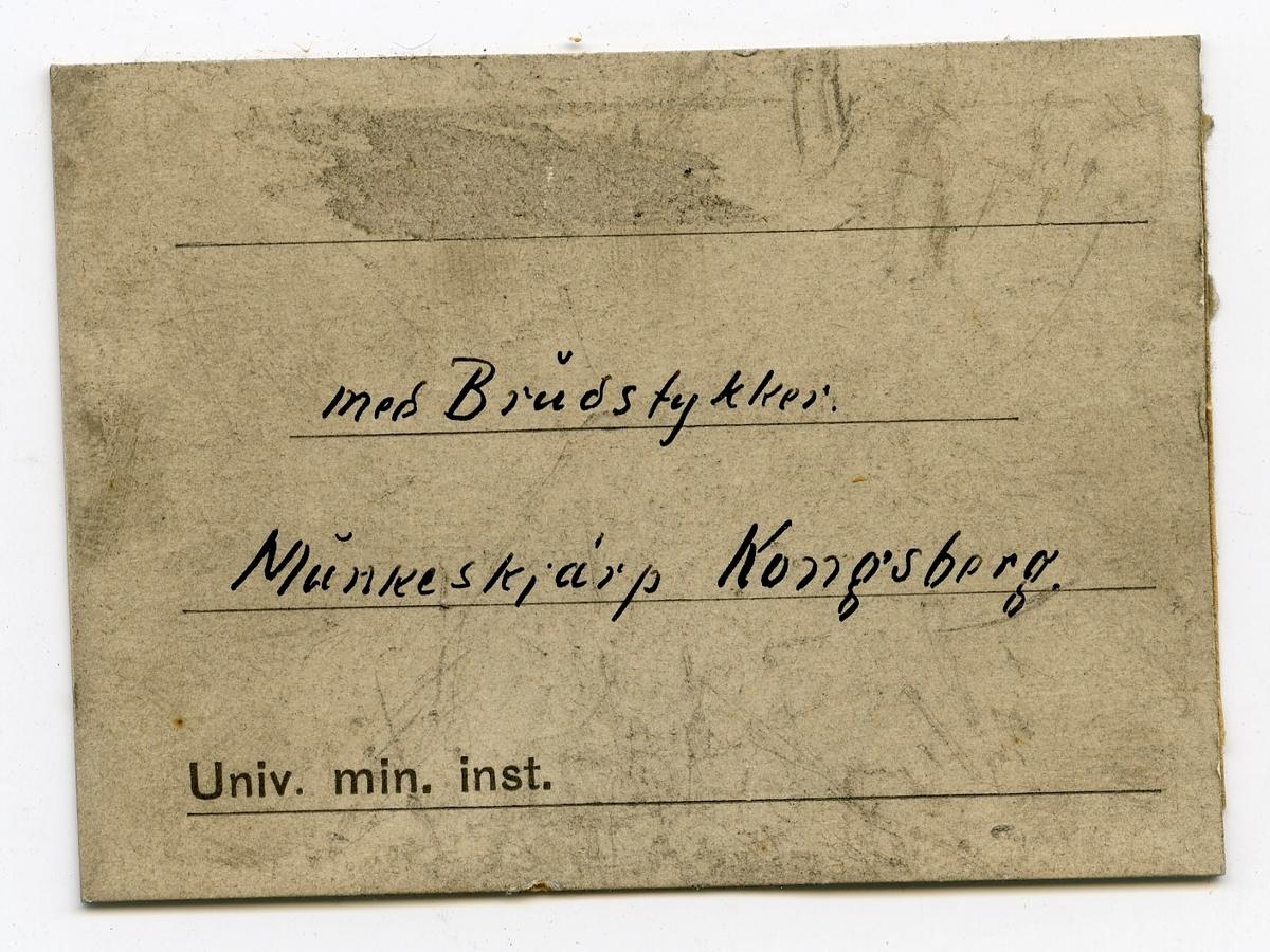 Etikett i eske: Med Brudstykker Munkeskjárp Kongsberg.  + papirlapp