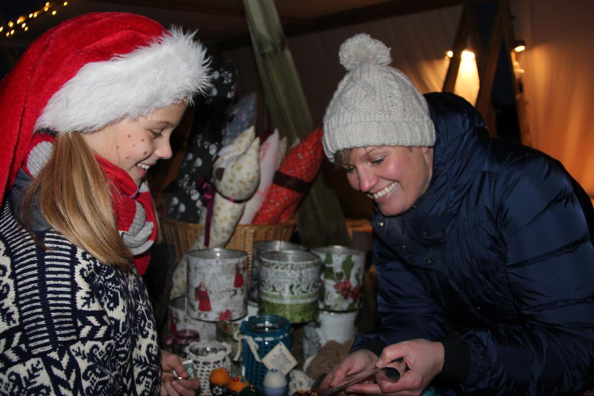 En voksen dame viser fram sine produkter til ei lita jente med nisselue