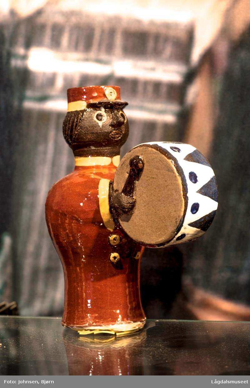Dekoren på lysestaken utgjør uniformen til musikanten. Utformelsen er en musikant med messinginstrument.