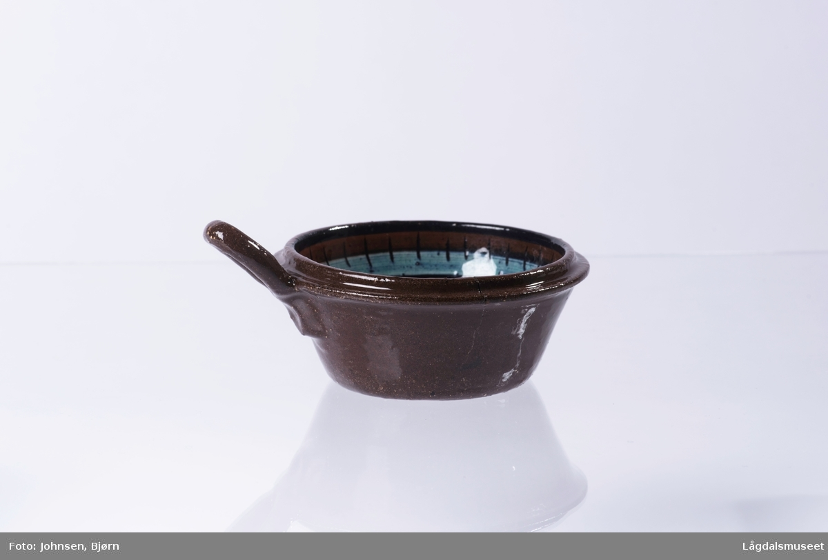 Koppe med dekorert innside. Dekoren er en blomst i bunnen av koppen og et ornament dekorert rundt toppen av koppen (på innsiden). Hanken er utformet for å kunne henge fra seg koppen.