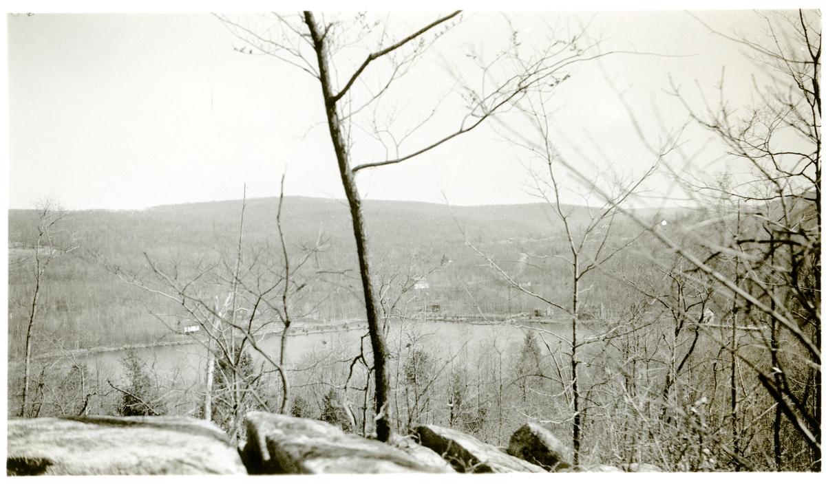 Motivet viser et vann med skogkledde åser rundt. Det ligger flere hytter/hus i i åsen rundt vannet. Bildet er tatt i Amerika i 1934.