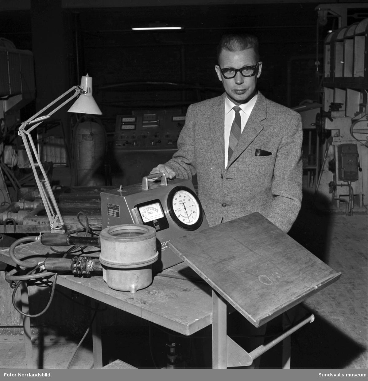En man visar upp någon slags tryckmätare vid Aluminiumkompaniet.