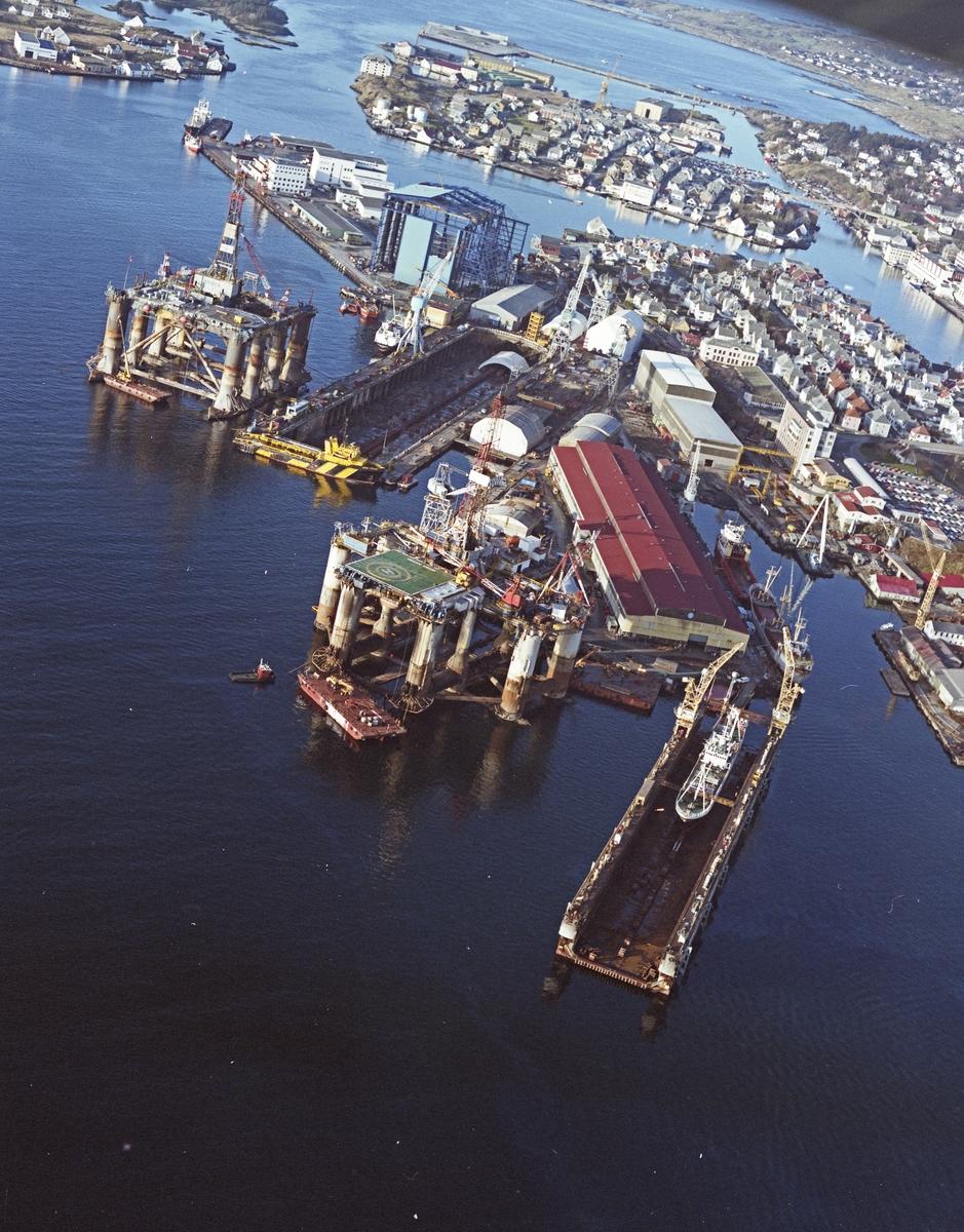 """Flyfoto. H.M.V. Oversikt over veftområdet med """"Nordsjøhallen"""". Hallen ser nesten ferdig ut fra utsiden. 2 platformer i sundet b.l.a. Odeco platformen """"Ocean Liberator""""."""