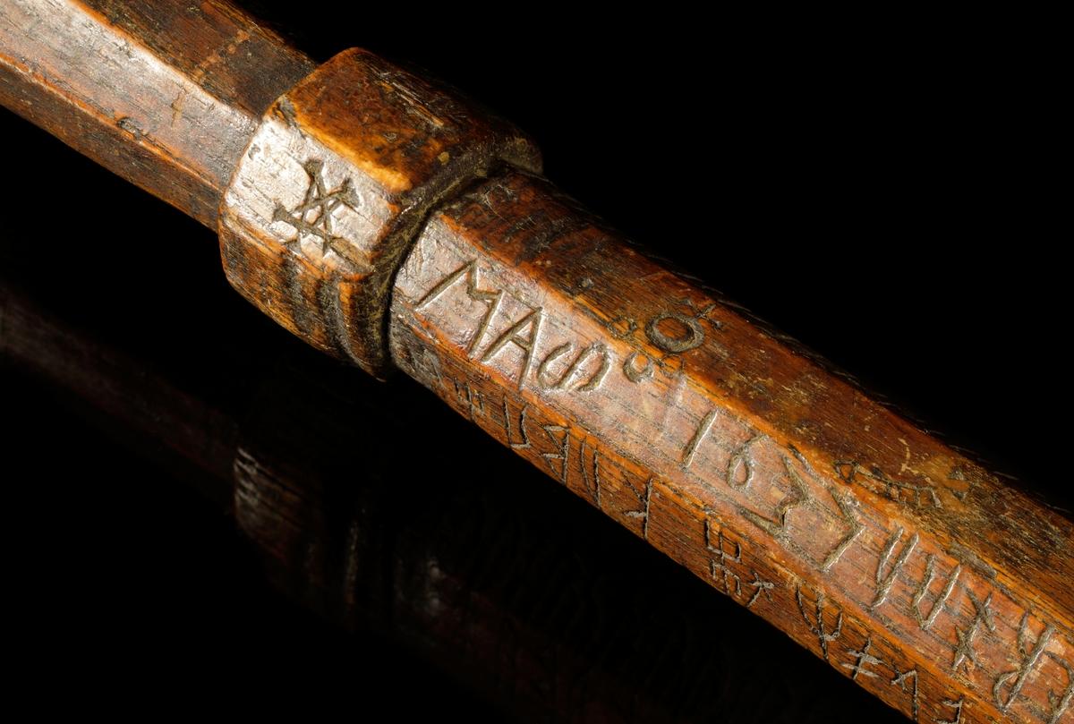 Kalenderstav i form av en stavformad, åttkantig runkalender. Längst ned sitter en metallhylsa som förstärkning om spetsen, samt under spetsen en inslagen dubb av järn.