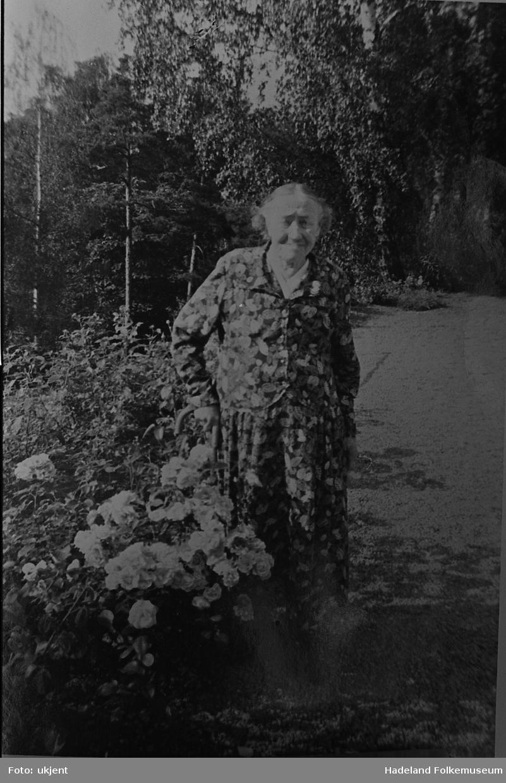 Eldre dame i blomstret kjole ved siden av et blomsterbed. Karen O. Foss