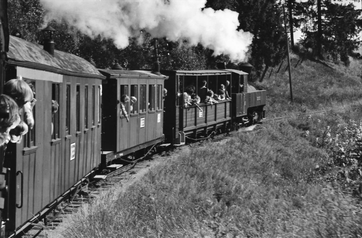 På vei oppover Sætrabakken fra Bingsfoss til Fossum med Tertitten, den smalsporede museumsjernbanen Urskog-Hølandsbanen sitt tog. Damplokomotiv nr. 4 Setskogen trekker toget, som består av vogn To1 ombygget til sommervogn, vogn Co1, BCo3 og fotografen er ombord i CFo5.