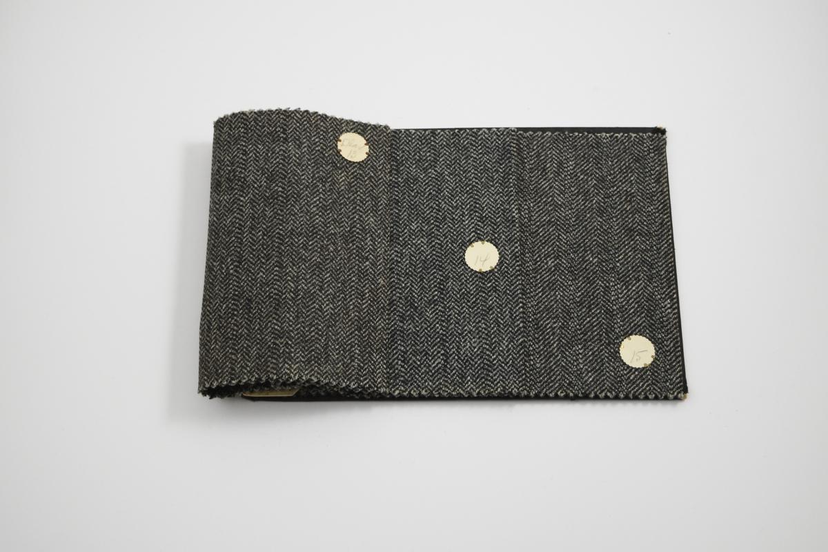 """Prøvehefte med 3 prøver. Middels tykke stoff med diskret fiskebensmønster - mønsteret er likt på forsiden og baksiden av stoffet. Stoffene ligger brettet dobbelt i heftet. Stoffene er merket med en rund papirlapp, festet til stoffet med metallstifter, hvor nummer er påført for hånd. Heftet har stiv bakplate og en papp-plate der heftet er stiftet som dekker ca. 5 cm forsiden. På pappen på forsiden er det en innskrift som indikerer at alle stoffene har kvaliteten """"Olav"""".   Stoff nr.: Olav/13, Olav/14, Olav/15."""