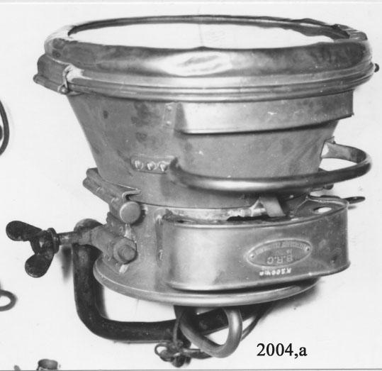 Strålkastare för acetylengas BRC no 255  Den är av franskt farbrikat och har tillhört flodångsprutan Phoenix, Karlskrona örlogsvarv, från början av 1900-talet.  Strålkastarens bakre del är cylindrisk. Den främre har formen av en stympad kon. På underkanten är den försedd med rör för intagning av gasen till en två-delad brännare i centrum. Härifrån förstoras ljuset genom runda glaslinser framför lågan och fortsätter genom strålkastarens glas och belyser föremålet. På överkanten och vid fästet för strålkastarglaset finns luftintag för förbränningen. På baksidan finns en rundad galje av järn med vingmuttrar för fastsättning till ställning ombord. Märkning på den ovala kopparplåten lyder: B.R.C. no 255 Lenticulaire Parabolique. Samt i svart: Phoenix. Användes för belysning.