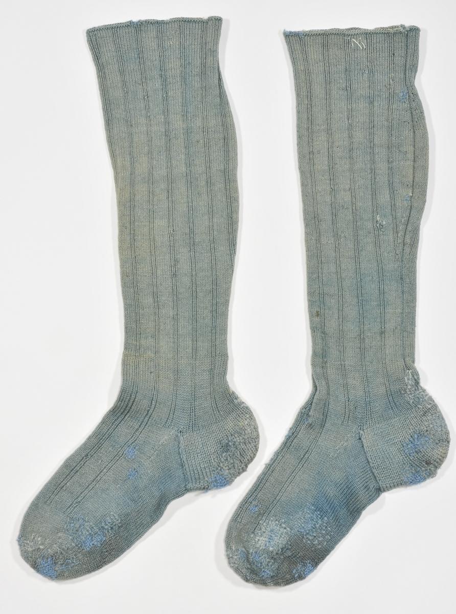Strømpe, lang heimestrikka strømpe i blågrønt ullgarn. Pedant til VFF 6430. Strikka 6 rette og to vrange . Stoppet  mange plassar i foten.