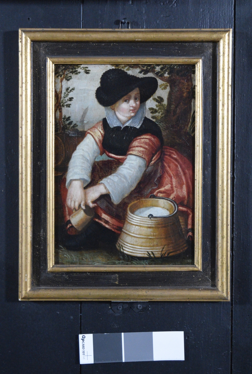 Bildet viser en stillesittende bondepike i rød kjole og sort hatt. I hendene som henger over knærne holder hun et krus. Foran henne står et lagget spann med melk i. I bakgrunnen ser man en tønne, trær og lengre borte en båt eller pram under seil.