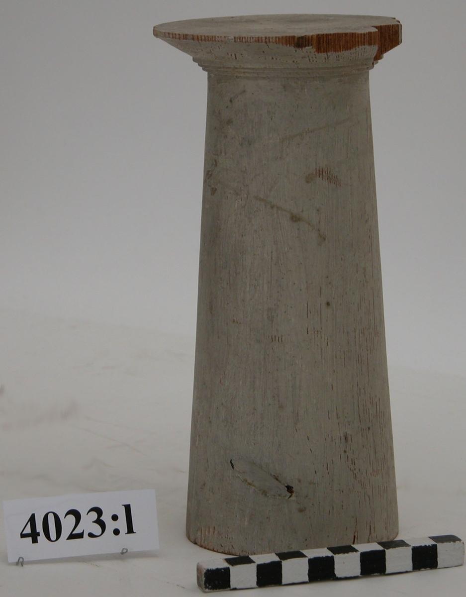 """Pelare, eller kolonner, släta och räfflade (Sju st halvkolonner, räfflade). 20 st modeller av trä avsedda som fasadprydnader. Pelarna är räfflade med halvcirkelformig basyta. De är vitmålade. Kapitälen är av närmast dorisk stil. Pelarna utgör modeller till gavelkonstruktion för nya inventariekammaren på varvet 1785-87. De sammanhängs troligen med en serie av gavelmodeller och pelare som finns i kistan i sal 1 och vid norra delen av väggen i samma sal. (K 2244)  Kolonn utan kannelering, med kapitäl. Målad i gråvitt. Olivgröna fuktprickar på en sida av kapitälet. Stor knagg. Märkt med blyerts på kapitäl: """"3""""."""