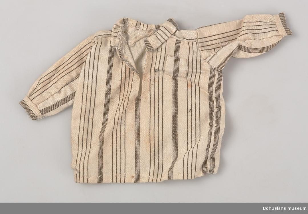 Tryckt mönster med vit botten och med gröna smala ränder. Halvlånga ärmar med linningar, krage, bröstficka.