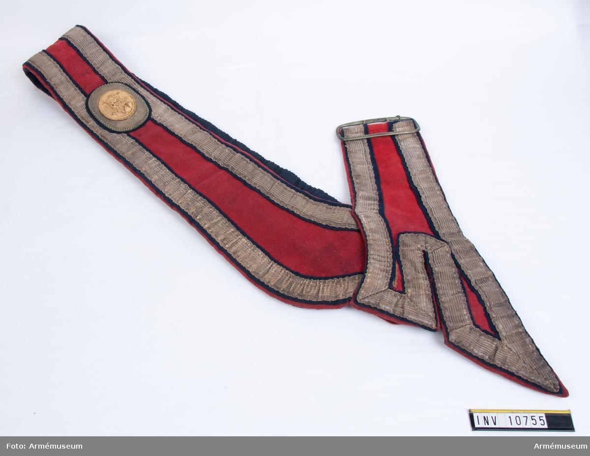 Grupp B.  Gehänget är av rött kläde med breda silverband och fodrad med blått tyg. Det är avsett för fanbärarens sidovapen.