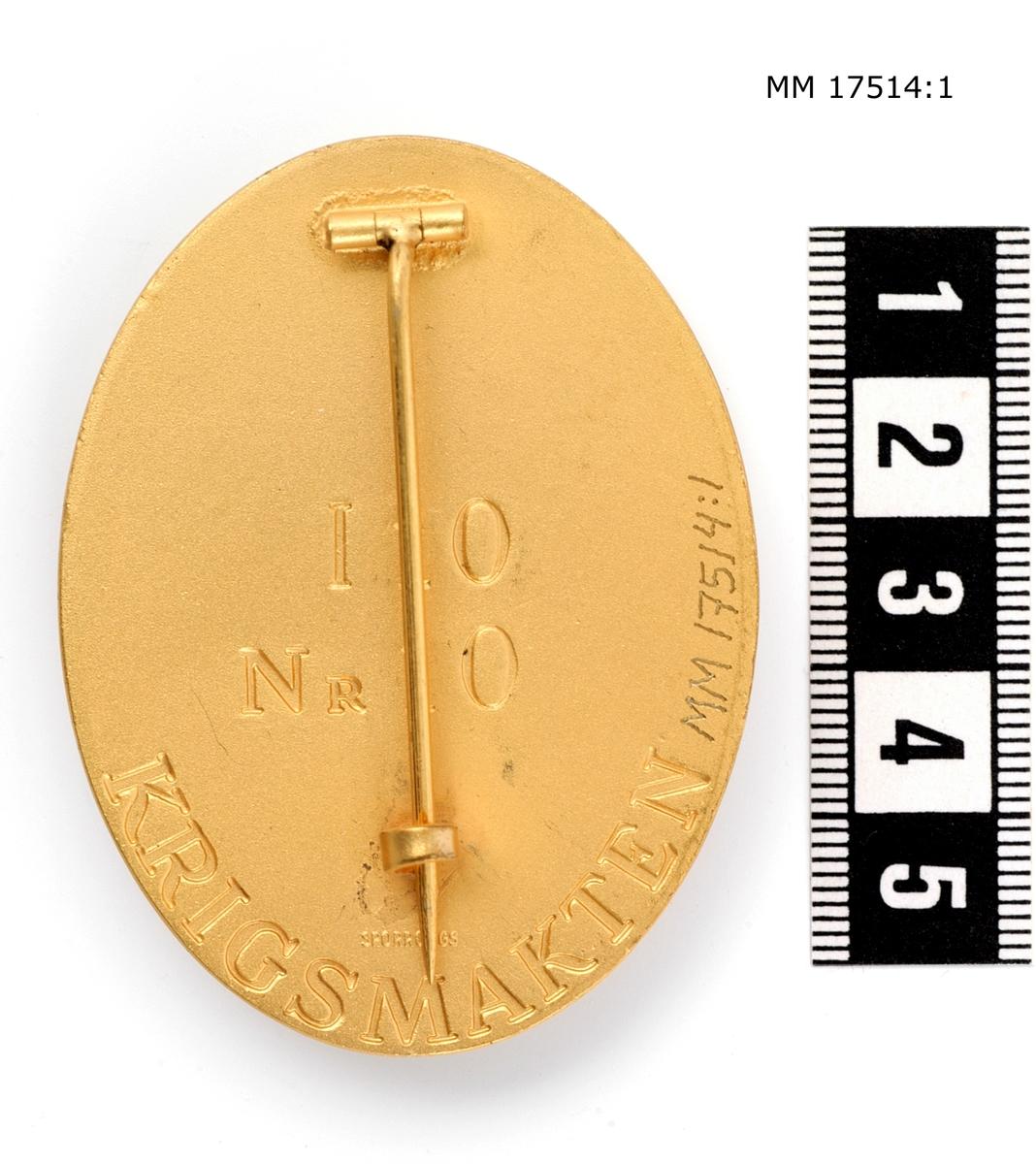 """Ovalt märke av förgylld metall. I mitten finns en krönt sköld med tre kronor, bakom skölden finns ett korslagdt svärd samt bila ombunden med spöknippe. Längst ned text: """"KRIGSPOLIS"""". Baksida text: """"10 Nr 10 KRIGSMAKTEN"""" (:2 """"Nr 11""""). Tillverkad av Sporrong. Försedd med vertikal nål."""