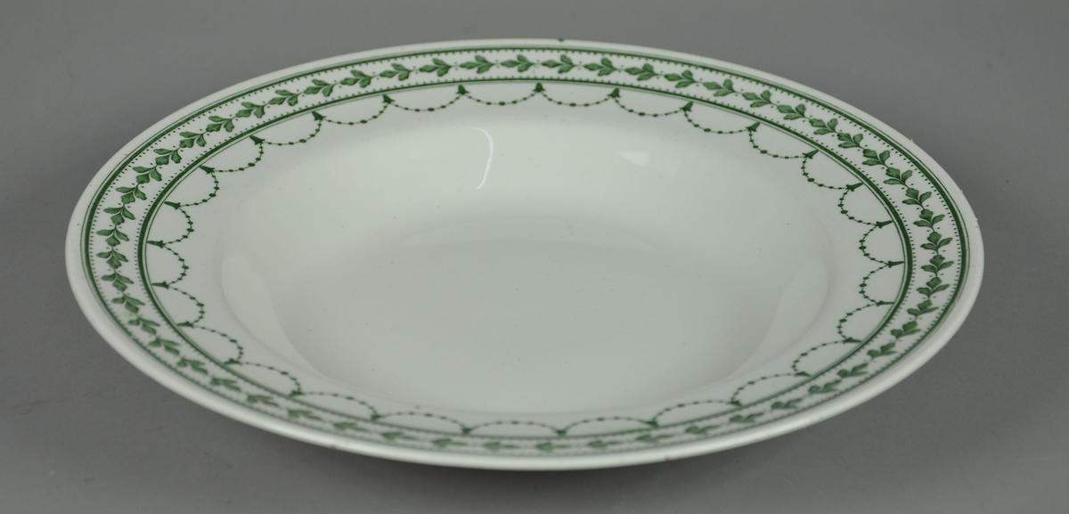 Rund og dyp suppetallerken av keramikk, steingods, med grønn bord. Borden består av eikekrans og guirlandere. Mønsteret heter Fontainebleau.