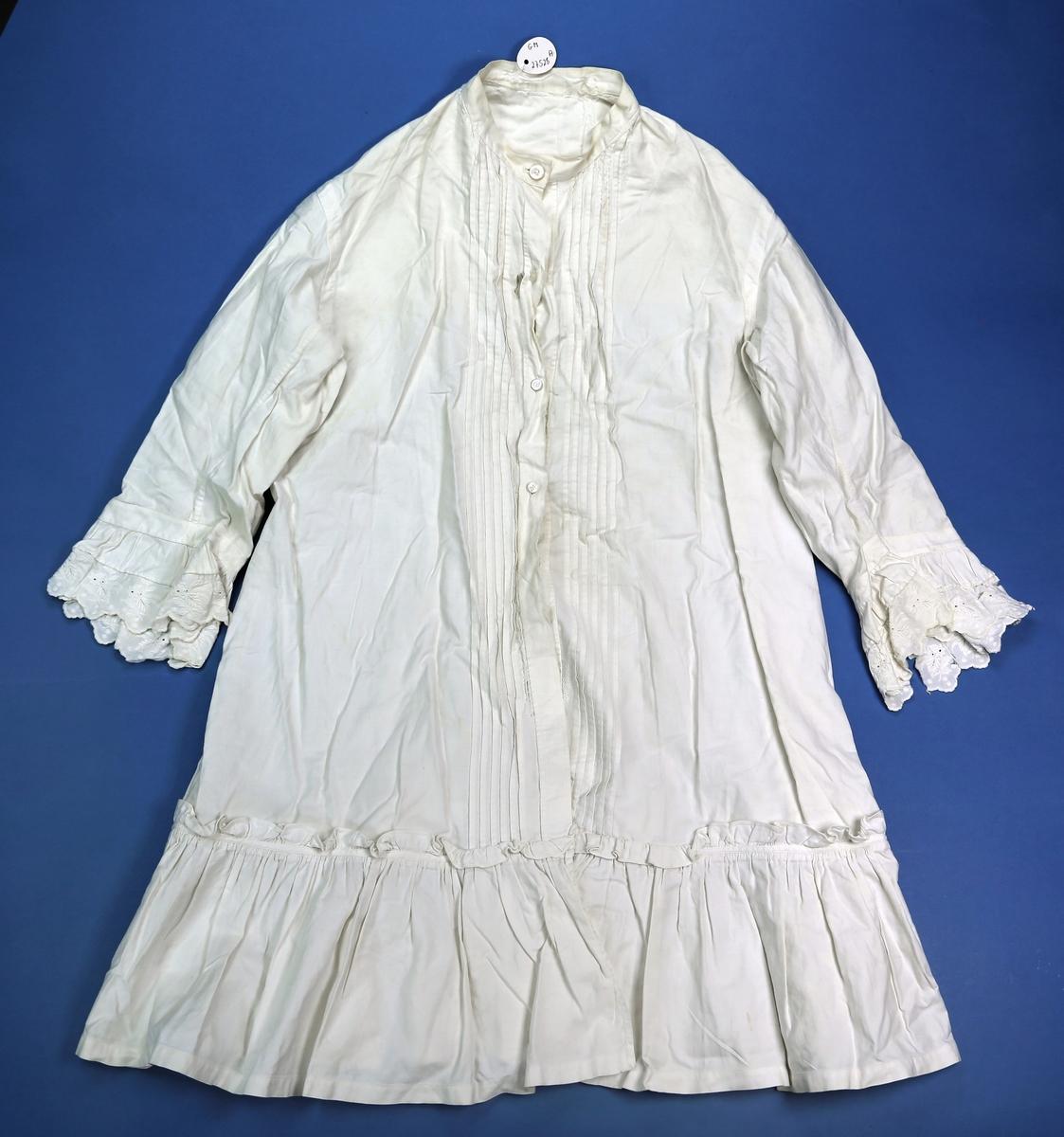 Kjole av kypertvevd bomull med foldet kandt nederst, knepping fra halsen og ned til foldekantent med vertikale legg langs åpningen, knapper av plast, blondekant rundt ermene