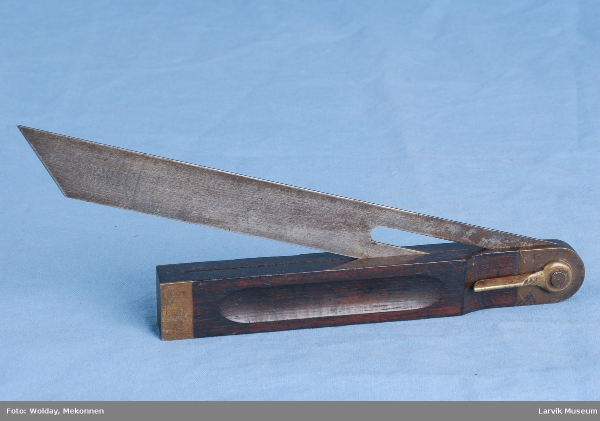 Teknikk: tredelens håndtak med uthuling for bedre gripetak, er forsterket i enden med messing beslag, vinkeljernet kan felles inn i tre-delen i 3/4 lengde, jernet har en slisse til feste for dreiepunktsskruen(av jern) med mutter og vrider i messing. Form: solid