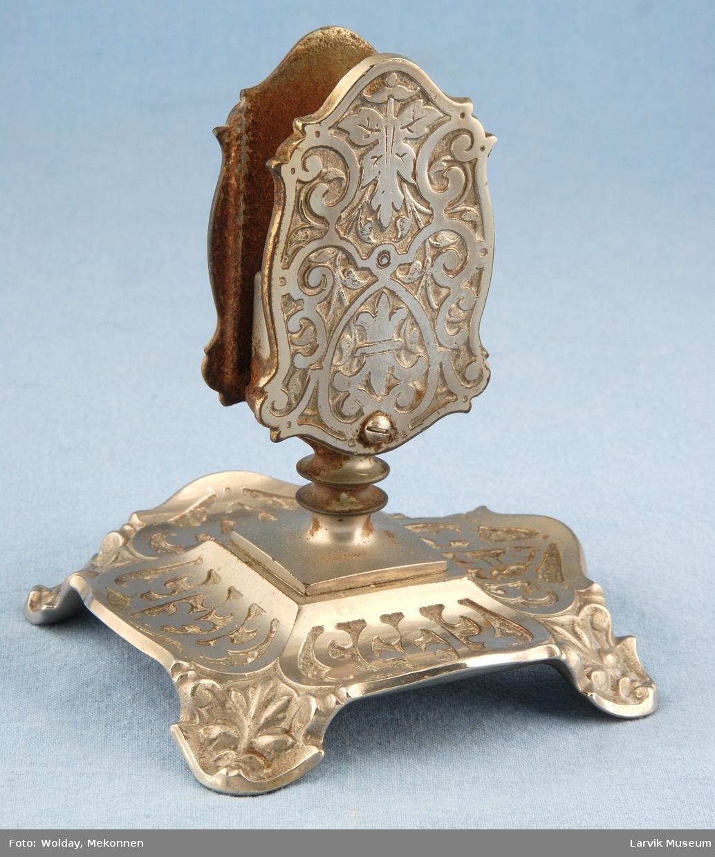 Form: En fot med snieklete relieffmønster opp fra denne står en holder passe til en fyrstikkeske. Denne også med relieffmønster.