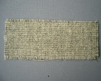 Vävprov, blåmelerat möbeltyg i ull vävt i panamabindning. Varp i grått 2-trådigt ullgarn; möbeltygsgarn. Inslag i grått 2-trådigt ullgarn; möbeltygsgarn. Två trådar tillsammans per inslag.