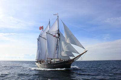 """Skonnerten """"Svanen"""" med tre master og for fulle seil ute på vannet, med norsk flagg."""