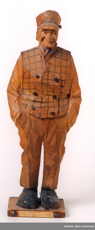 KLM 39255:6. Skulptur, av trä, gubbe i skärmmössa med svartrutad väst, svarta rockknappar och skor. Står på fotplatta med nitad papperslapp med påskrift Smålänning. Signatur på fotplatta: C J Trygg, Norrköping 1912.